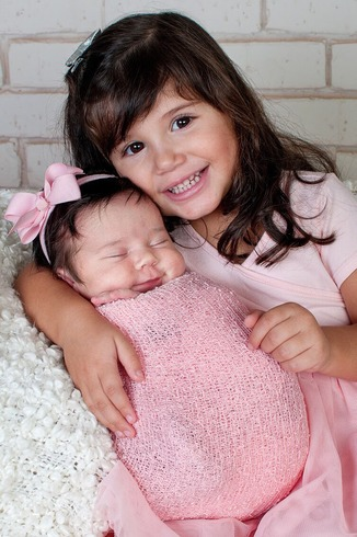 Newborn smiles with big sister