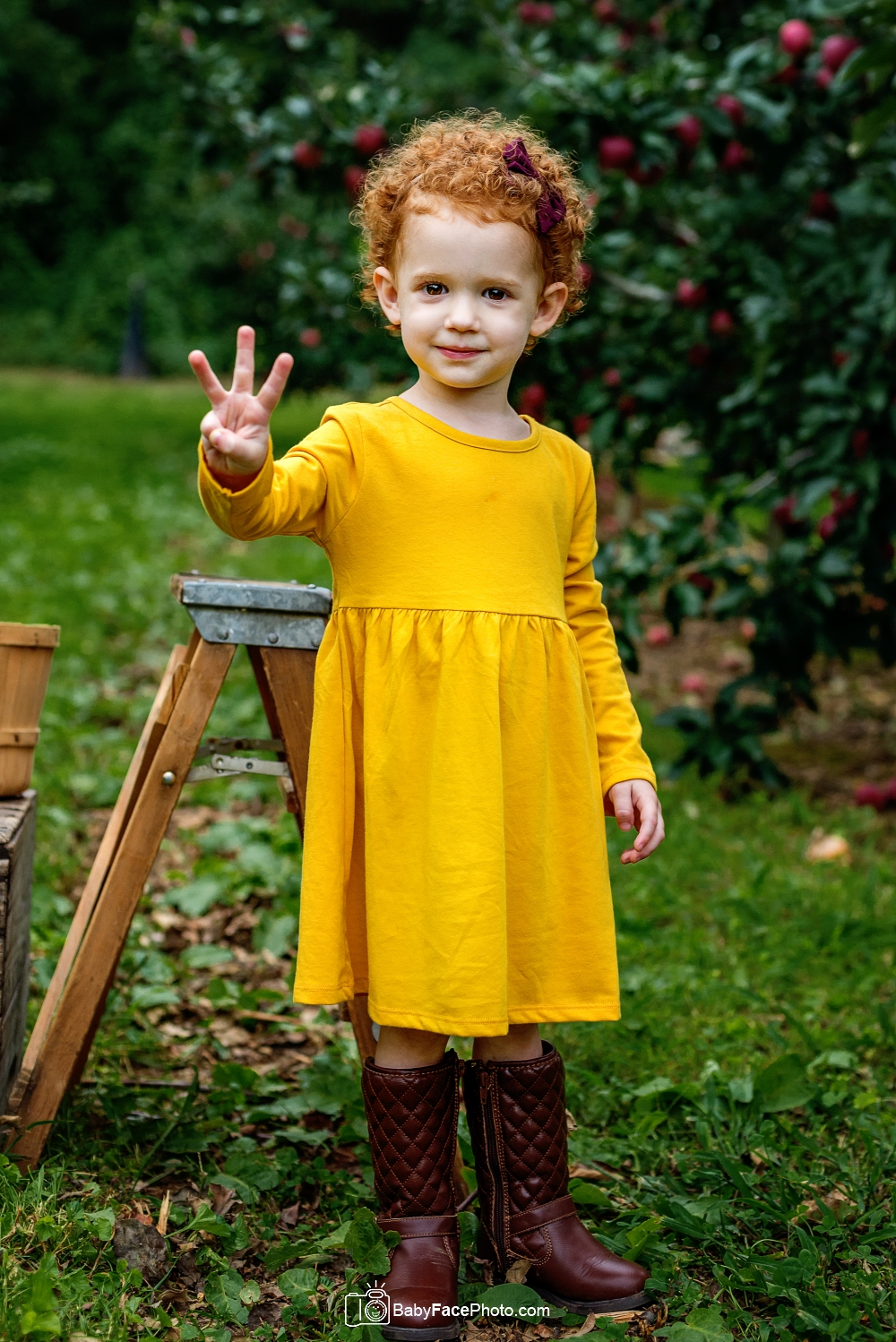 3 year old girl in apple orchard holding up 3 fingers