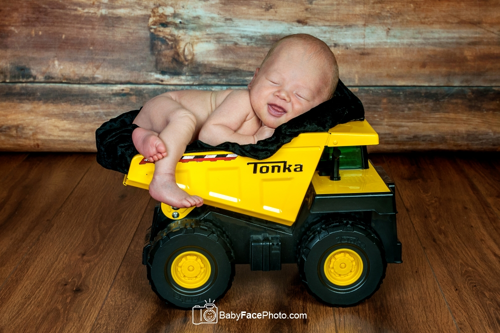 newborn boy smiling in Tonka truck