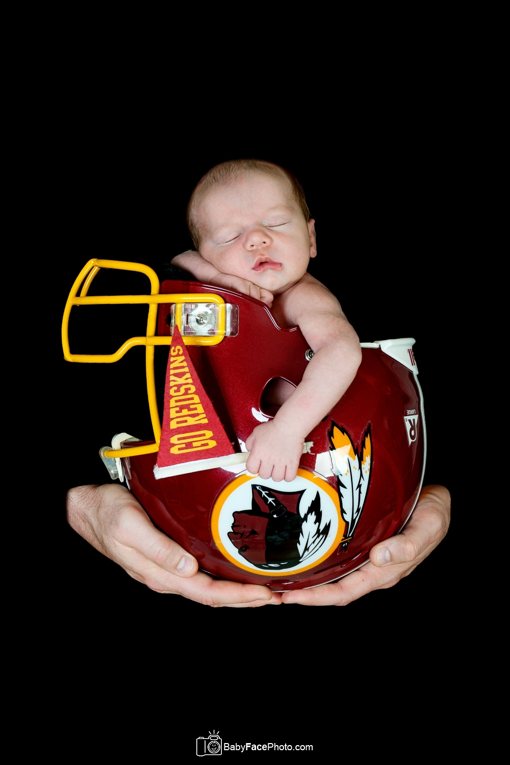 newborn in Redskins helmet