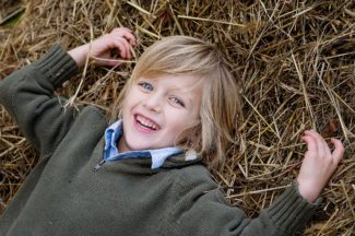 boy laying in straw