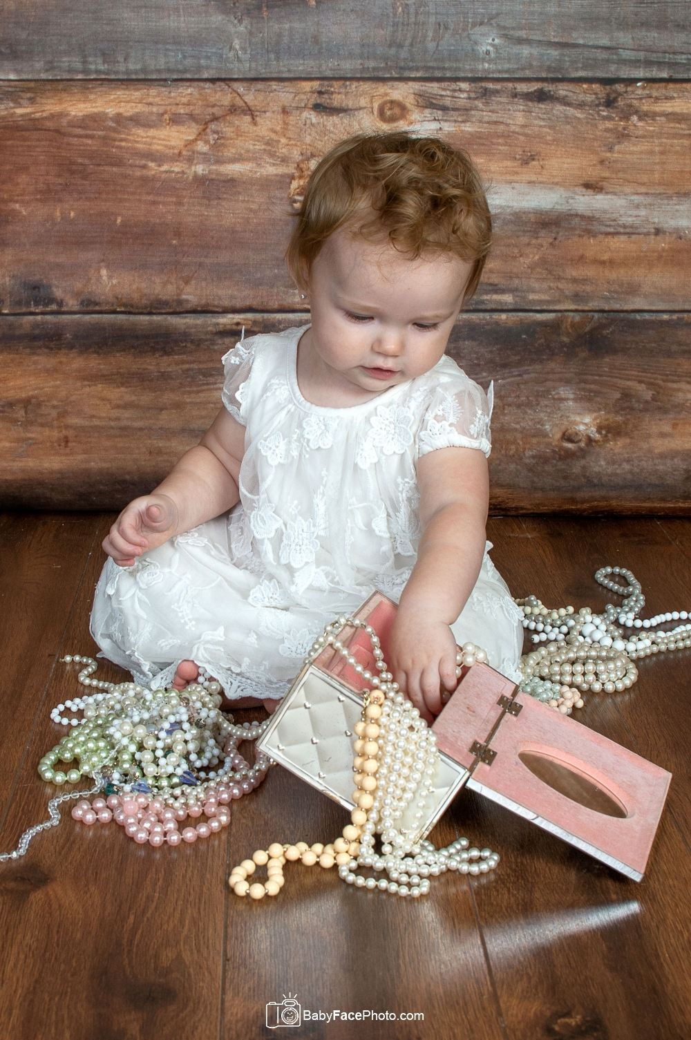one year old girl playing with jewelry box and beads