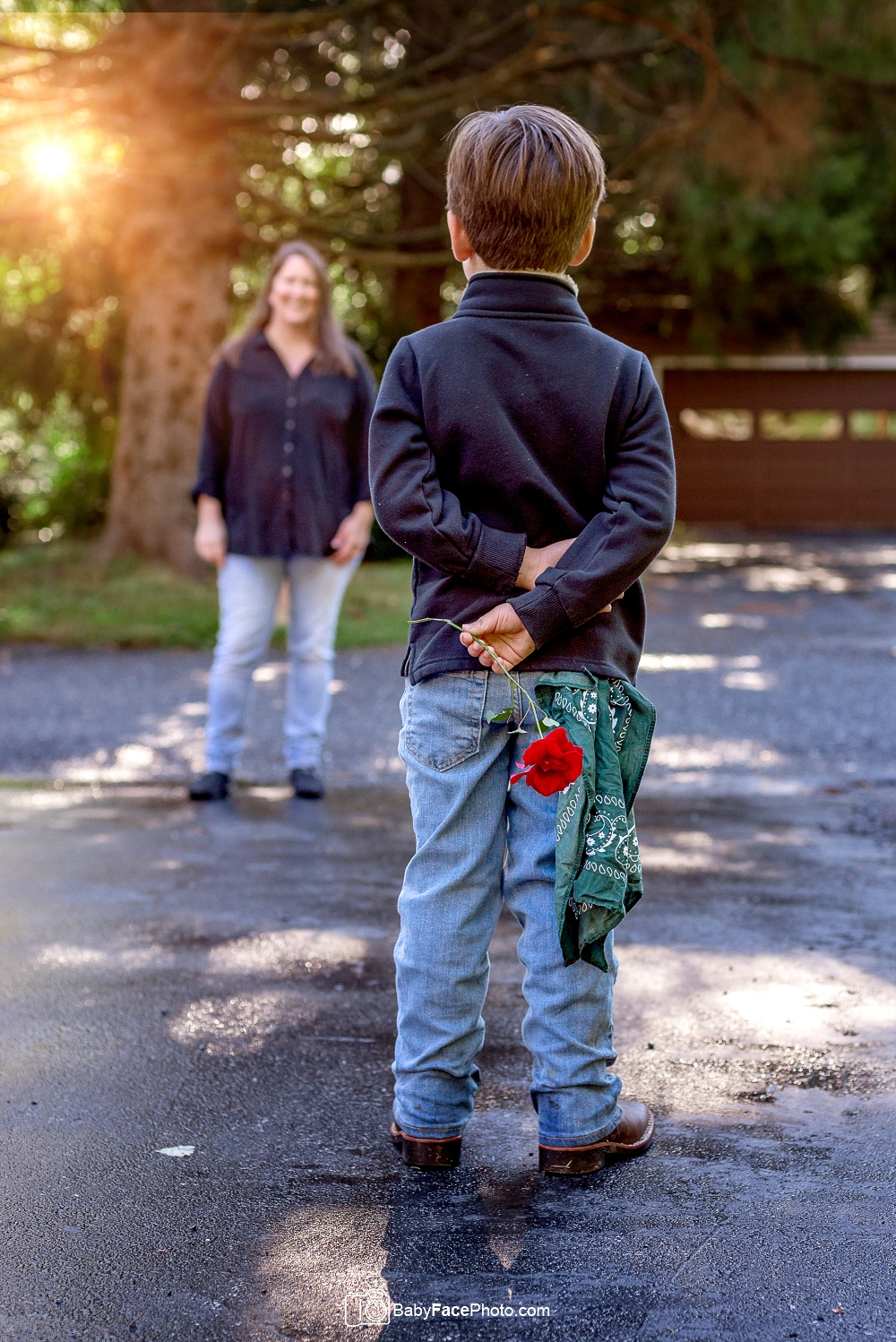 boy hiding rose behind his back for mom